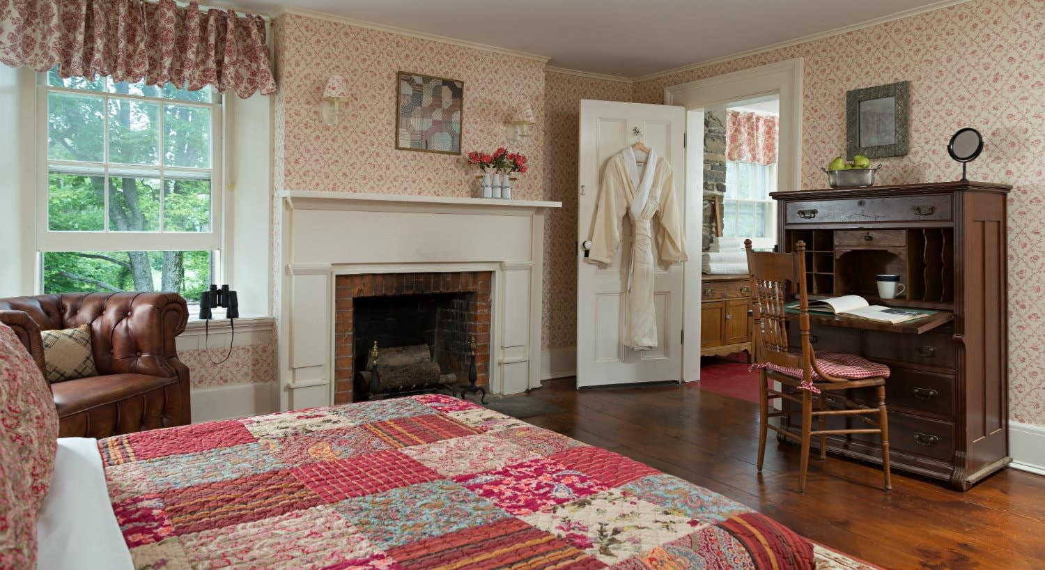 Spacious cozy room with warm wood floors, large windows, red floral quilted bed, fireplace and antique secretary