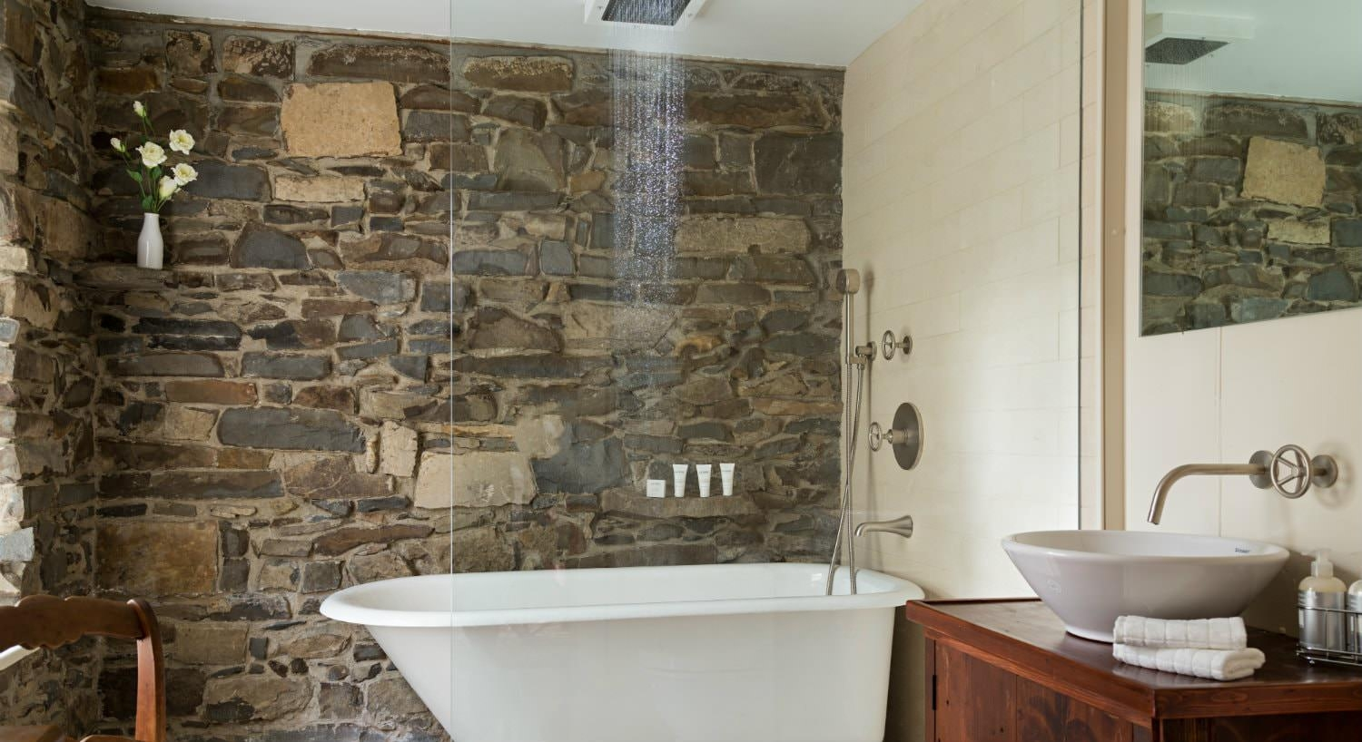 Stone and wood walls, claw foot tub with rain shower head and glass door, vanity with white vessel sink