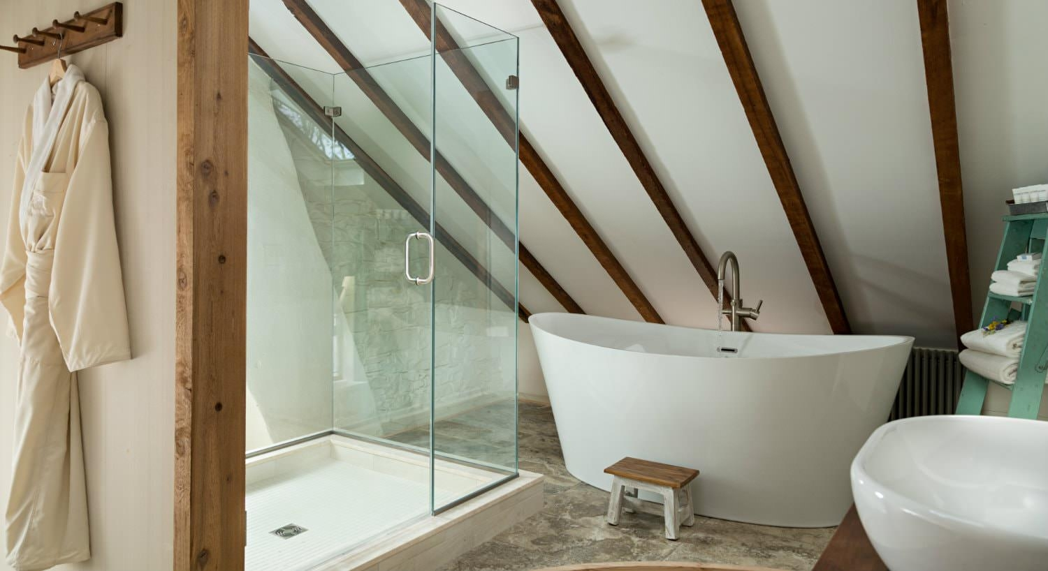 Vaulted white bathroom with walk-in shower with glass doors and modern freestanding tub