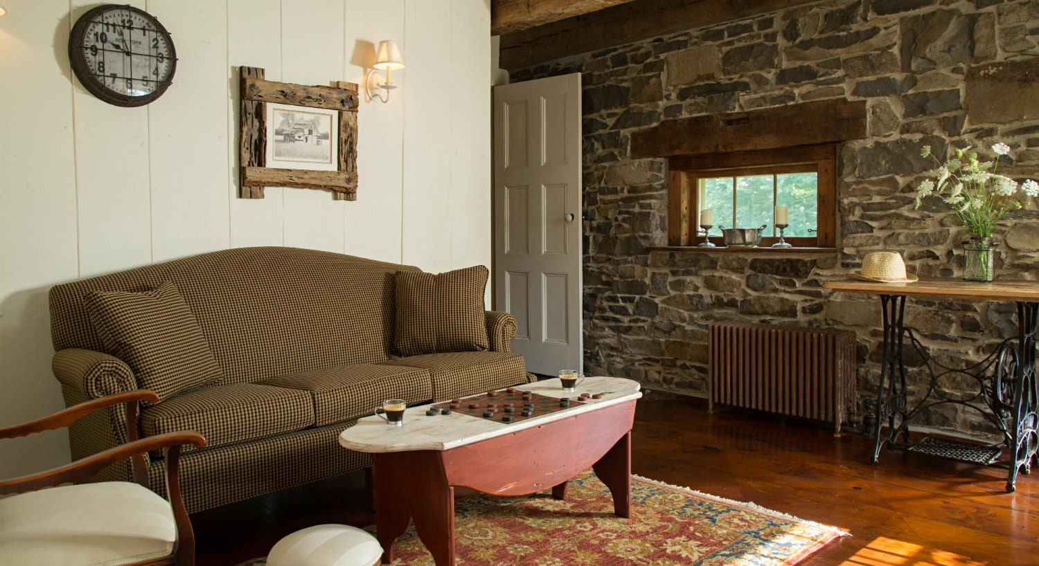 Rustic sitting room with white painted wood walls, stone wall with small window, sofa and chair around painted coffee table