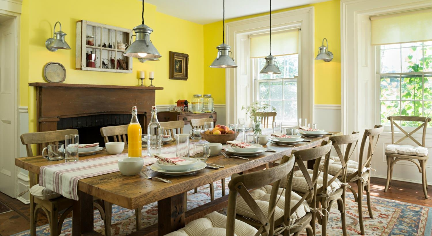 Spacious yellow dining room with fireplace, large windows, rustic table for eight set for breakfast