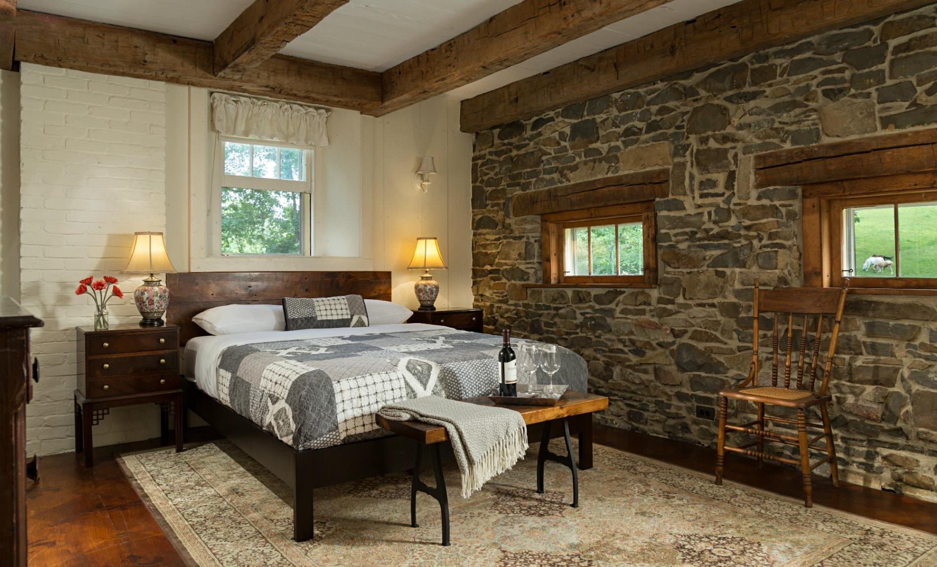Spacious white room, exposed rustic beams, stone wall with two small windows, light colored rug, gray and white covered bed