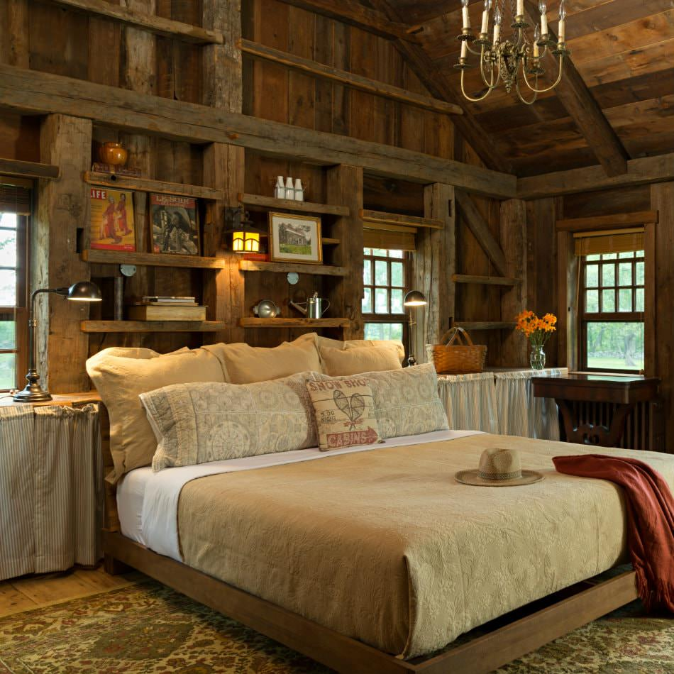 Rustic wood room with several windows, open shelves with collectibles, and large bed with tan bedding