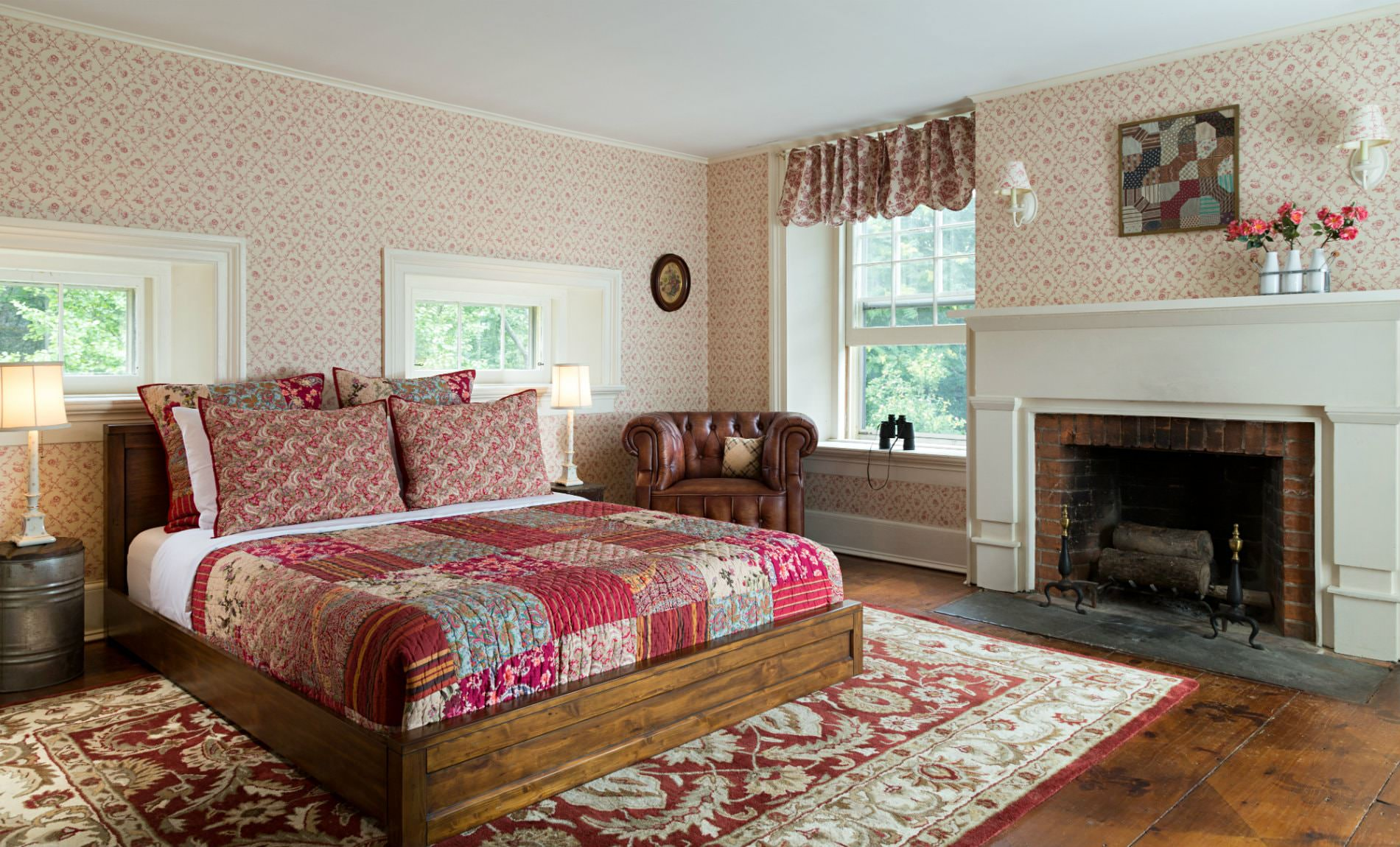 Spacious cozy room with warm wood floors, several windows, red floral quilted bed, fireplace and brown leather club chair