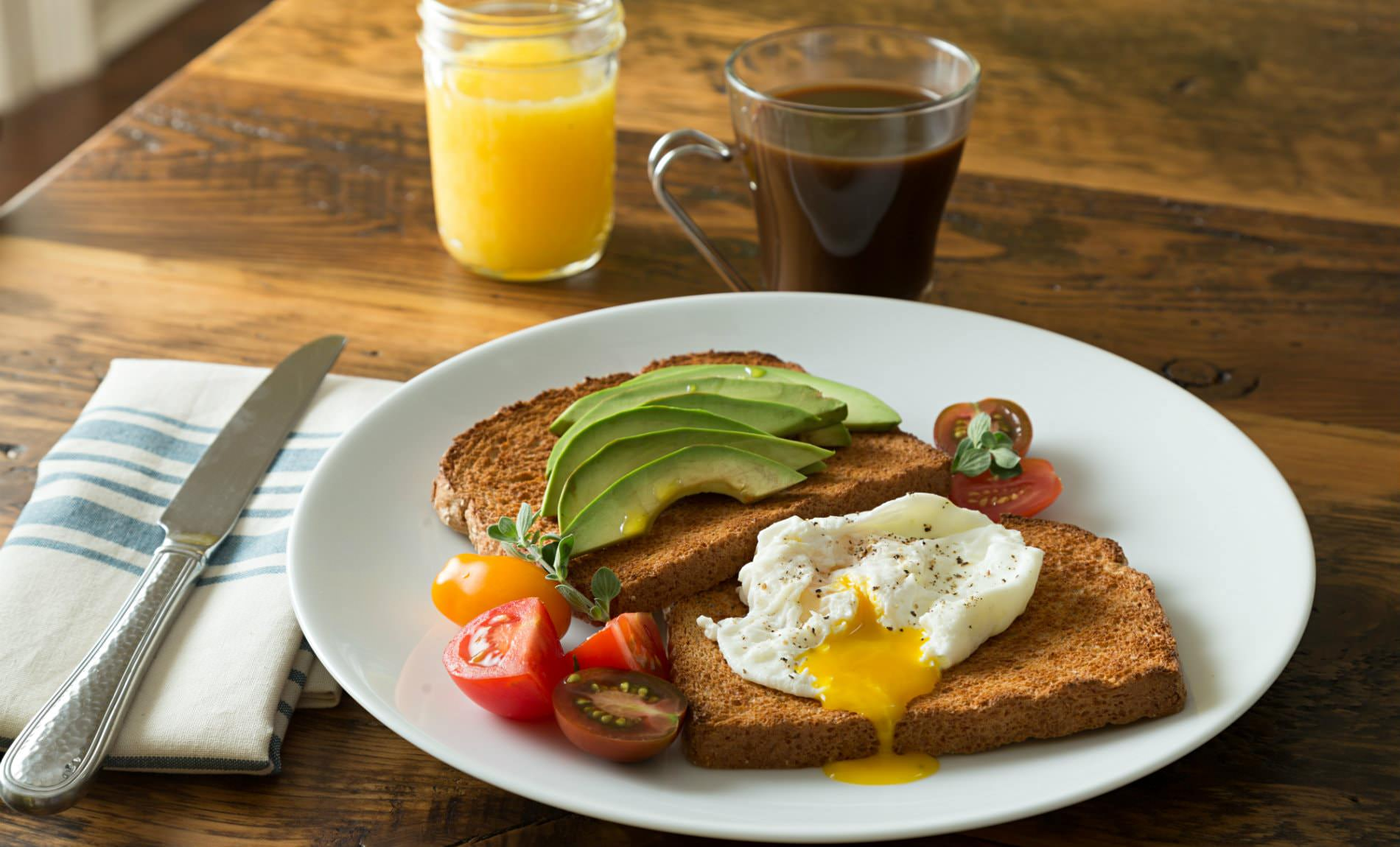 White plate of toast, avocado slices, fried egg and sliced cherry tomatoes, glass of juice and cup of coffee