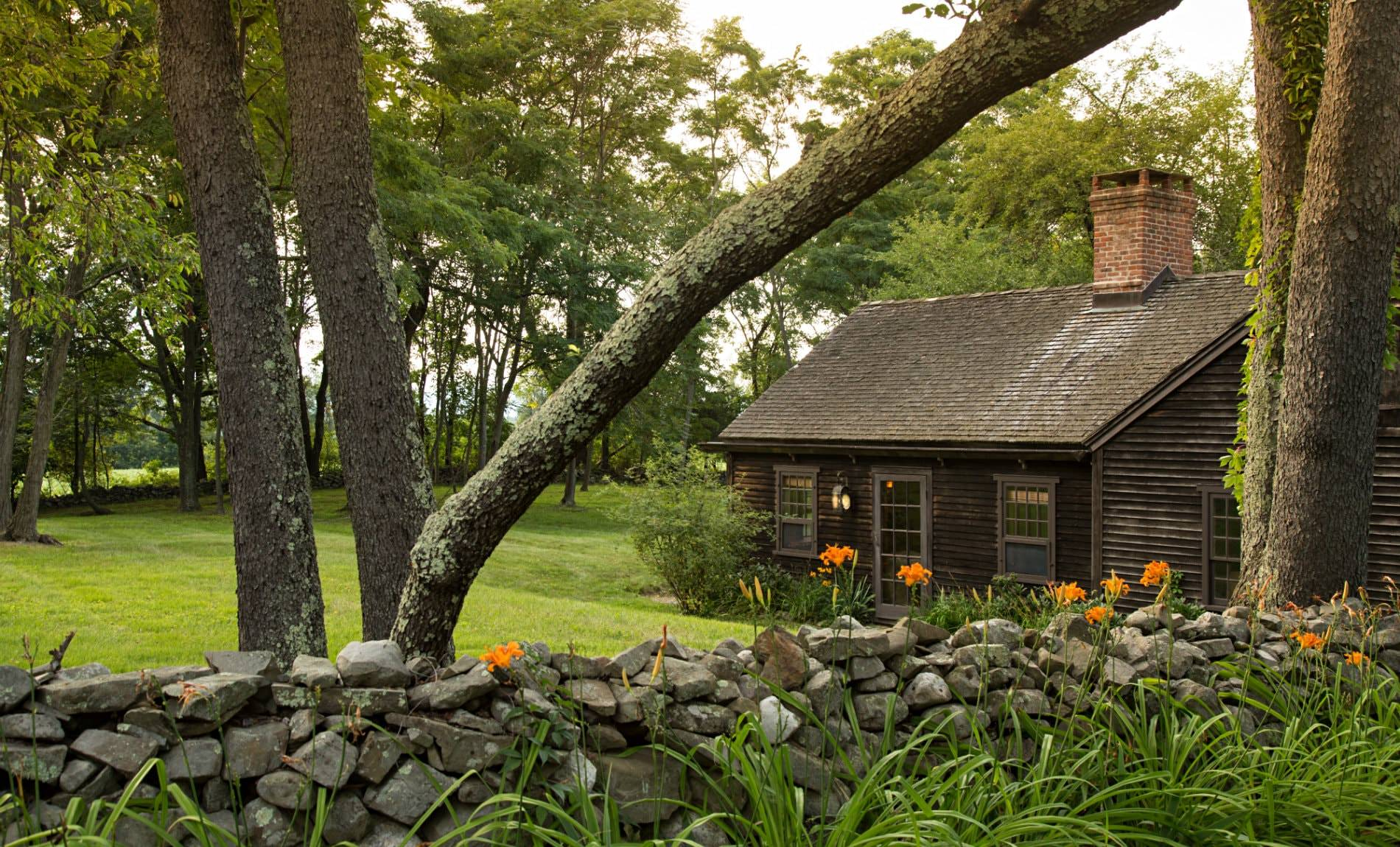 Rustic brown cabin surrounded by green grass, a gray stone wall and trees