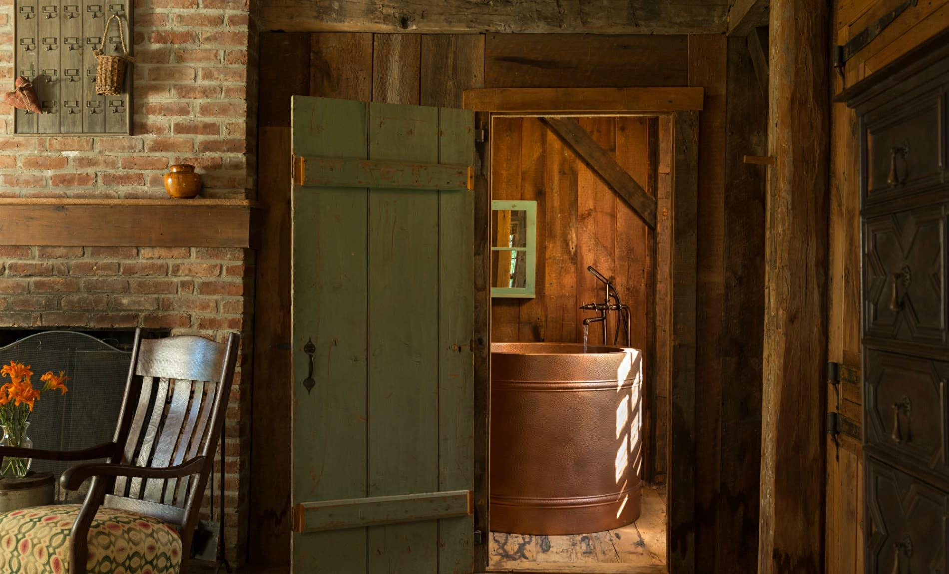Rustic wood and brick room with view of round copper tub through an open green door