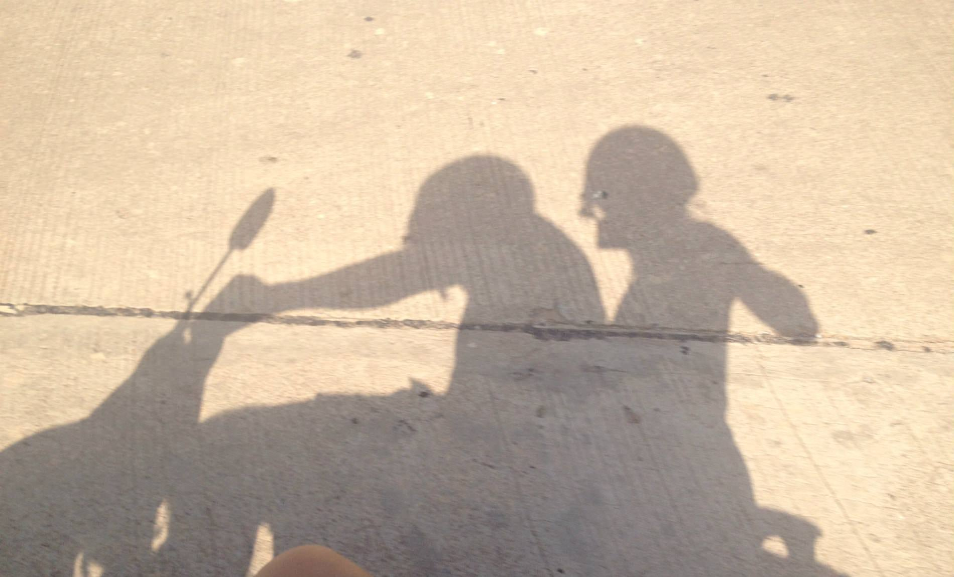 Gray shadow on concrete of two people riding a motorcycle