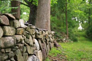 Low gray stone wall surrounded by green grass and trees