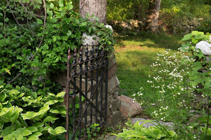 Stone base with a black wrought iron gate surrounded by grass, plants, bushes and trees