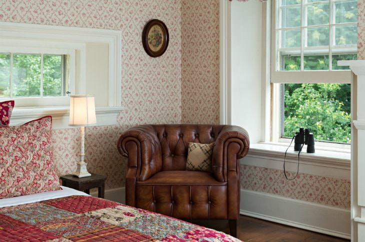 Cozy room with red and white papered walls, deep window sill with binoculars, red quilted bed and brown leather chair