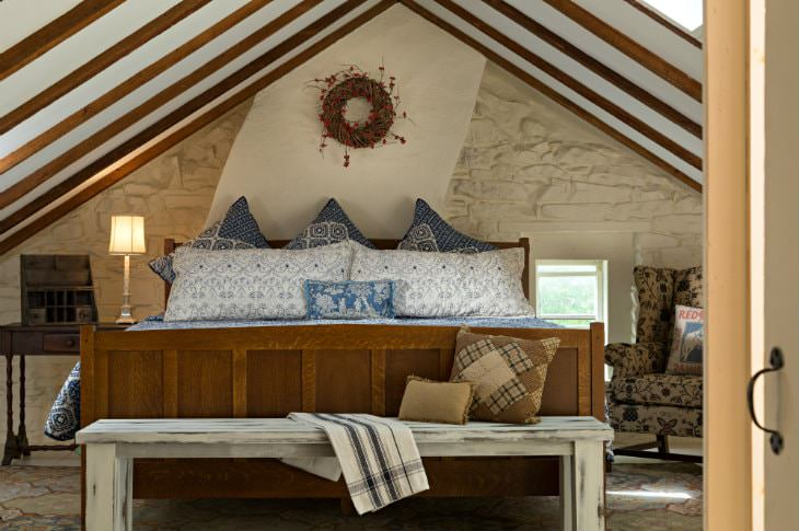Large wood bed with blue and white bedding against a white stone wall under vaulted ceiling with exposed beams