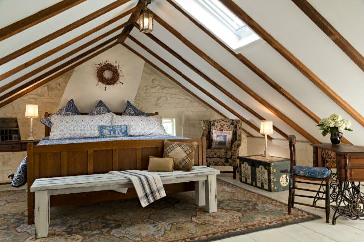 Vaulted attic room with one white stone wall, large wood bed with blue and white bedding, and wood floors