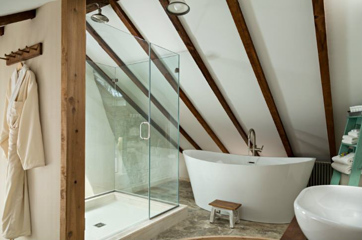 Rustic vaulted bathroom with walk-in shower with glass doors, modern freestanding tub and exposed beams