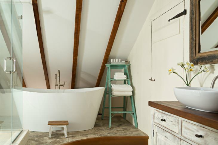 Vaulted white bathroom with walk-in shower with glass doors, rustic vanity with modern white sink and modern freestanding tub