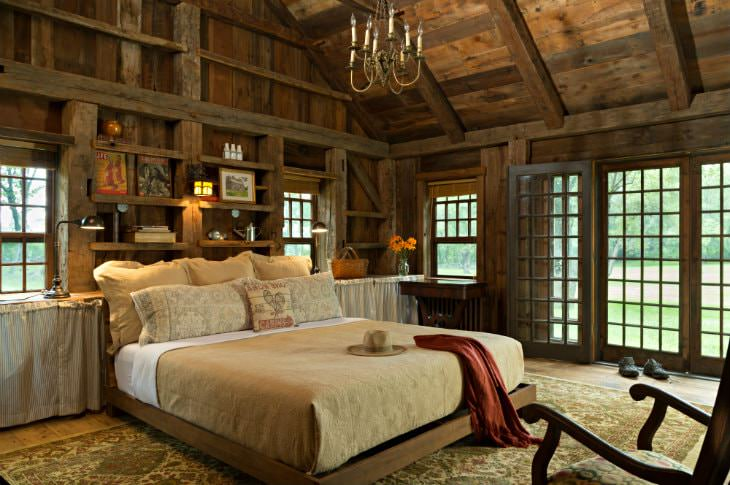 Vaulted rustic wood plank room with exposed beams, double-hung windows and French door, and large bed with tan bedding