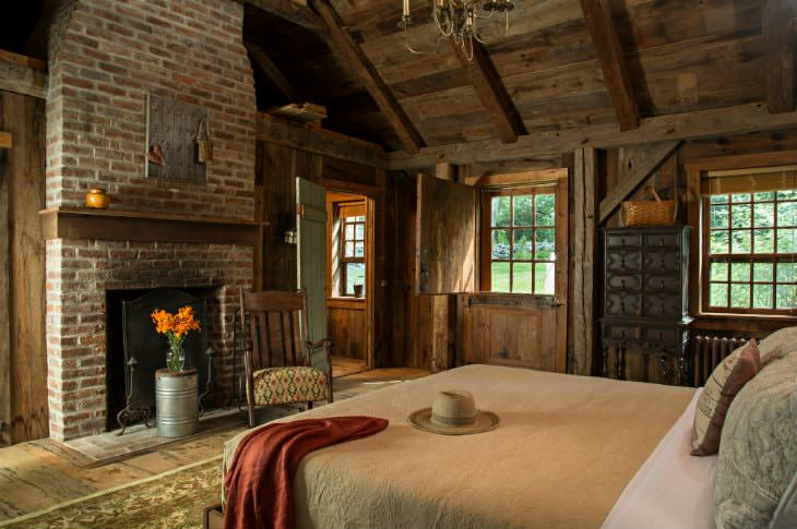 Cozy rustic room with wood floor and walls, vaulted wood ceiling, brick fireplace, double hung windows and large bed