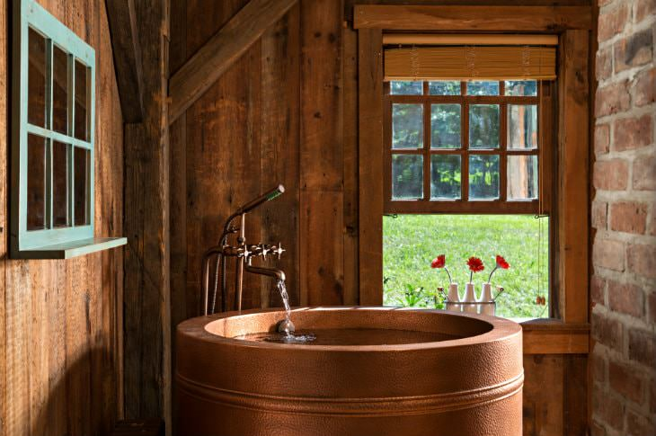 Wood and brick room with round copper tub, antique faucet and open window with three white vases of red flowers
