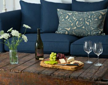 Blue sofa and rustic coffee table topped with fresh white flowers, cheese board with fruit, wine bottle and wine glasses