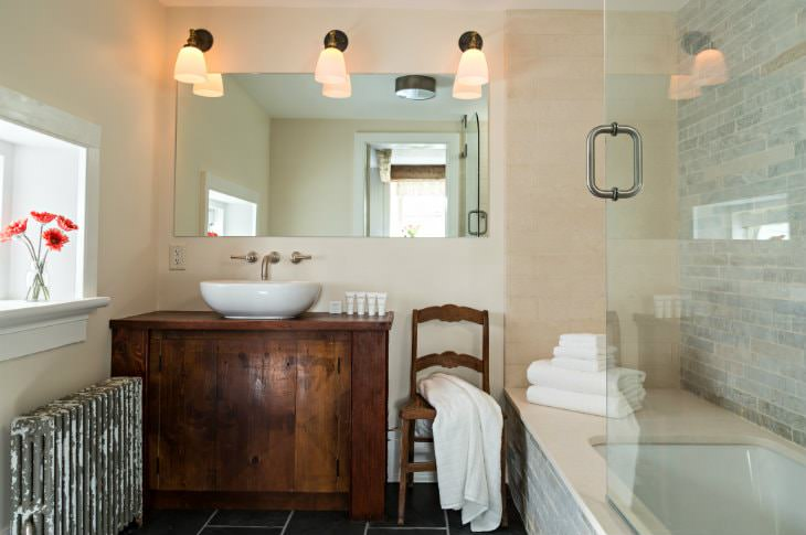 White bathroom with dark tile floor, rustic wood vanity with modern white sink, large mirror and sconce lighting