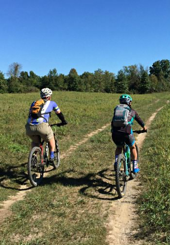 Man and woman riding bikes along dirt path in an open meadow surrounded by trees and blue skies