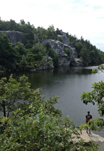 Man standing on stone ledge overlooking body of water surrounded by hills covered in rock and trees