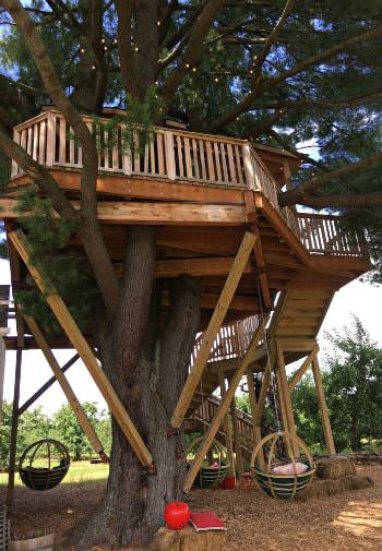 Large wood treehouse with railing and stairs and green basket swings