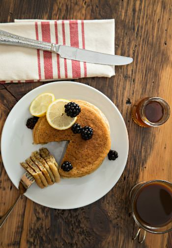 Table topped with a white plate of pancakes and fresh berries, a cup of coffee and cup of maple syrup