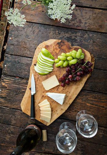 Rustic table topped with cheese board with grapes and apple slices, bottle of uncorked wine and two wine glasses