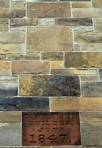 Brown stone builder wall plaque dated June 1847 surrounded by brown, grey, gold and black stone