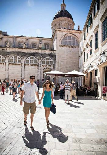 Man and woman holding hands walking through stone courtyard amidst a crowd of people and old stone buildings