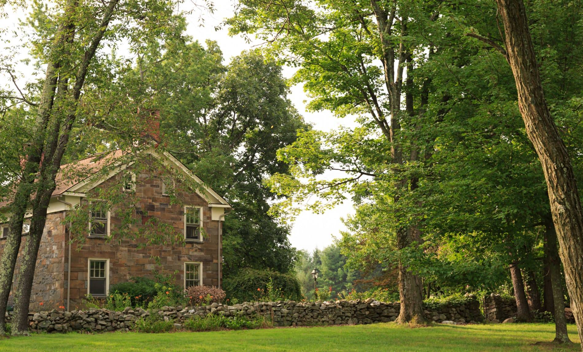Brown stone building and stone wall running along property surrounded by green grass and trees